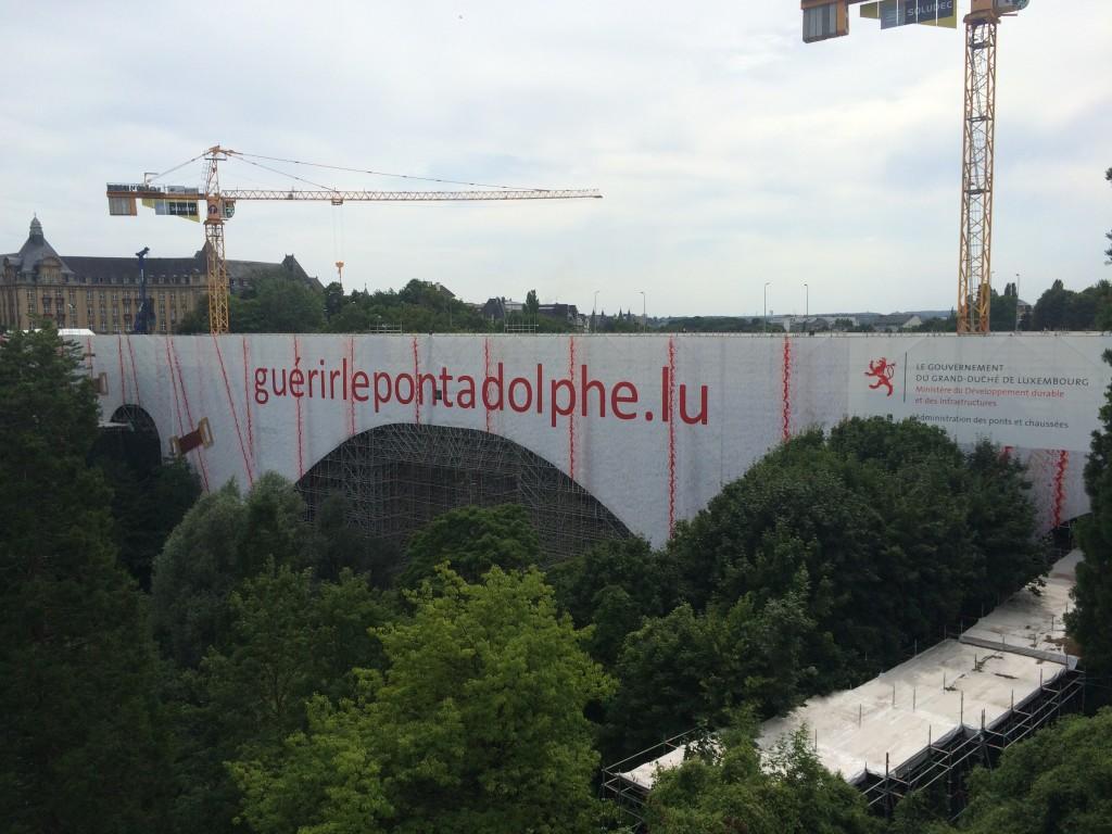 "The URL on the scaffolding translates as ""Healing the Adolphe Bridge"""